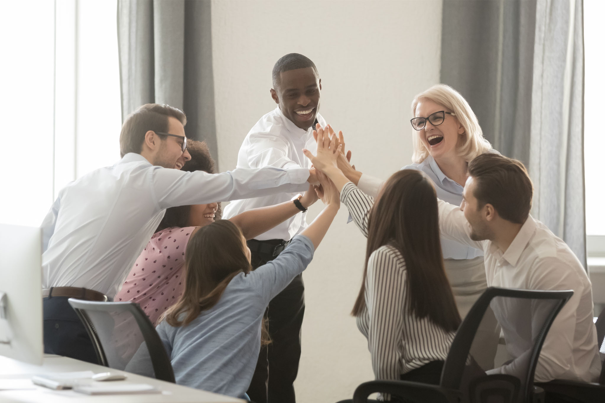 Happy multicultural employees business team engaged in teambuilding giving high five hands celebrate corporate success motivated by shared win great result together in office, trust integrity concept
